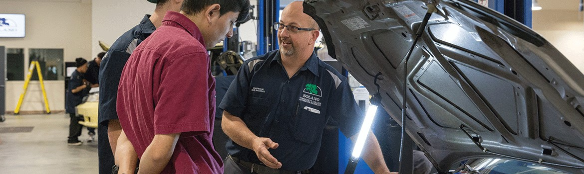 Automotive website main picture. Professor Ricky Marshall discusses auto technology with students.
