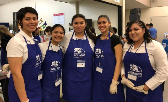 Students with aprons working at the crab feed