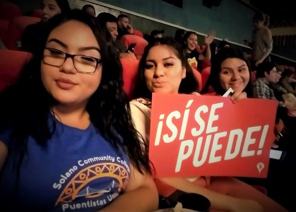 Three Puentistas Listening to Dolores Huerta holding a sign that says si se puede.